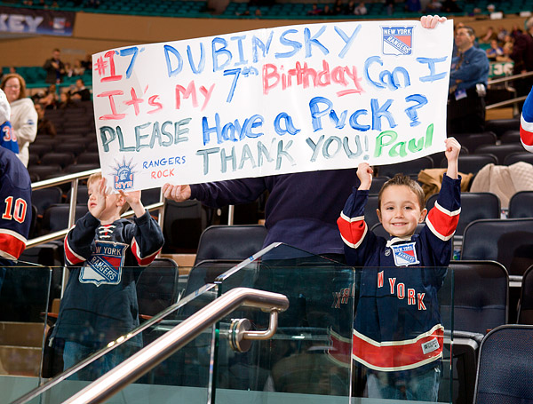 A young fan hopes for a puck during pre-game warmups