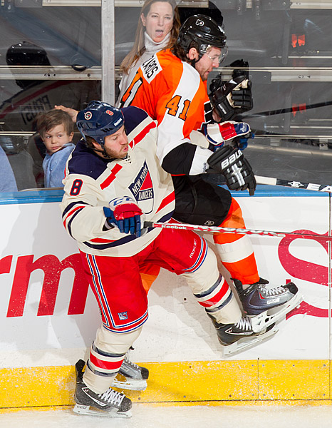 Ranger Brandon Prust checks Flyer Andrej Meszaros into the boards