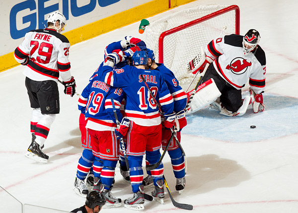 Carl Hagelin gets mobbed by his Rangers teammates after scoring the game winning goal against Martin Brodeur and the Devils