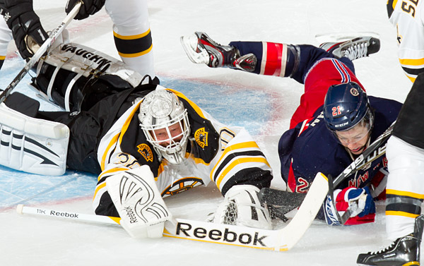 Bruins goalie Tim Thomas makes a save next to a diving Derek Stepan