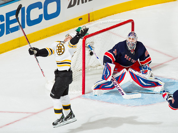 The Bruins' Patrice Bergeron jumps for an airborne puck while Rangers goalie Henrik Lundqvist looks on