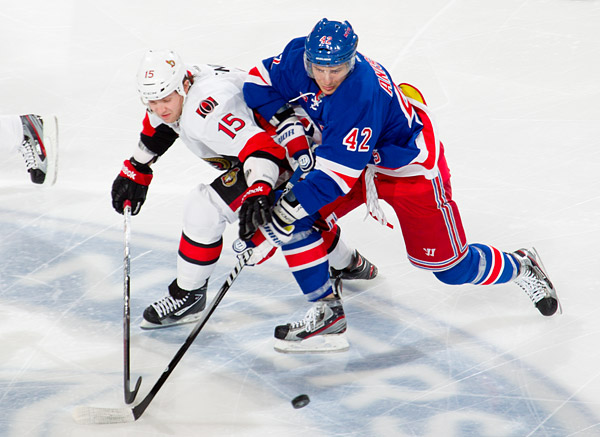 Ottawa's Zack Smith battles for the puck with New York's Artem Anisimov
