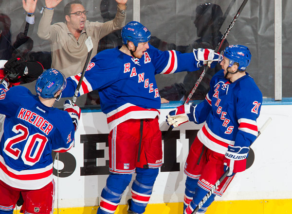 New York's Marc Staal celebrates his goal with teammates Chris Kreider and Derek Stepan