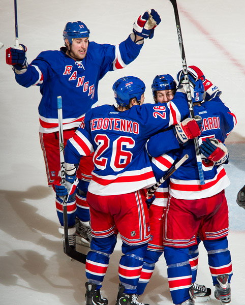 Brandon Dubinsky, Ruslan Fedotenko and Brandon Prust celebrate with Dan Girardi after he scores his second-period goal, the eventual game winner