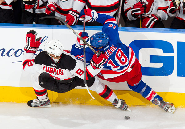 New York's Marc Staal gets physical along the boards with New Jersey's Dainius Zubrus