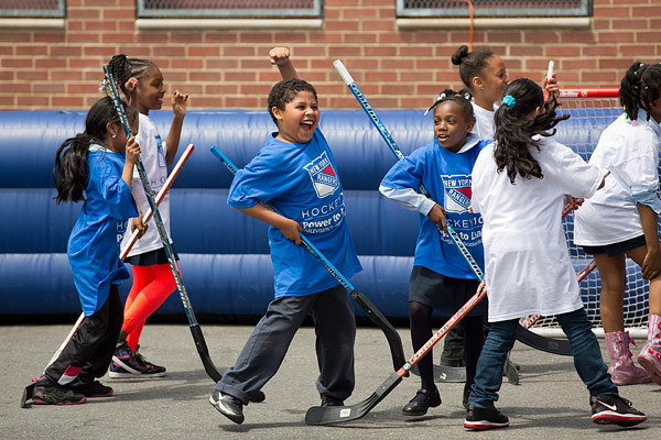Students in the New York Rangers Power to Learn Hockey 101 program celebrate a goal at their year-end tournament.