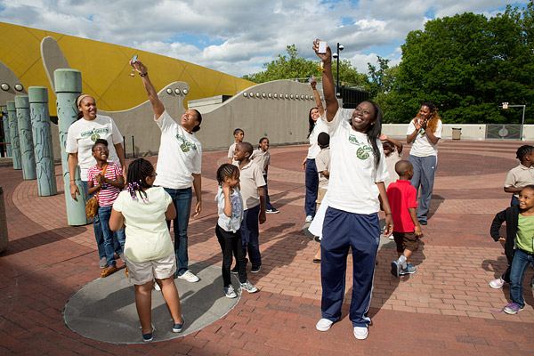 New York Liberty basketball players Kelley Cain, Alex Montgomery, Plenette Pierson, Essence Carson, and Kara Braxton and kids from the Garden of Dreams Foundation run solar energy experiments on the roof of the Brooklyn Children's Museum