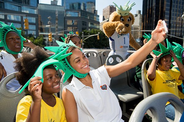 New York Liberty basketball player Leilani Mitchell snaps a photo with a child on a Garden of Dreams Foundation double decker bus tour through midtown Manhattan