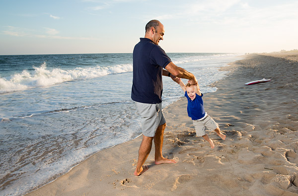A father plays with his son on the beach in the Hamptons.