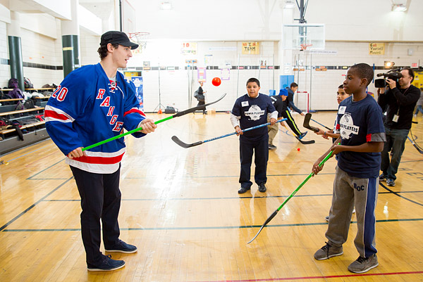 New York Rangers hockey player Chris Kreider teaches stick-handling skills to kids at a Garden of Dreams Foundation Power Players Street Hockey launch event a community center in the Bronx.