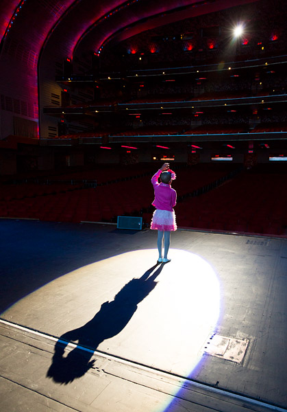 A young singer rehearses on stage for the Garden of Dreams Talent Show at Radio City Music Hall.