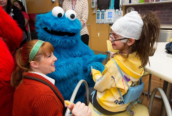 Sesame Street's Cookie Monster and music teacher character Jenny visit young patients at a New York City hospital.