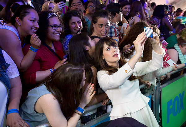 Actress Zooey Deschanel takes a selfie with fans at the 2014 Fox Upfront in New York City