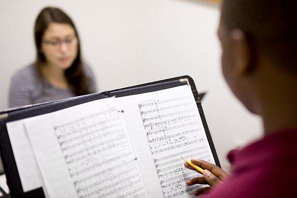 A student looks over sheet music as he receives individual voice instruction at Highbridge Voices in the Bronx.