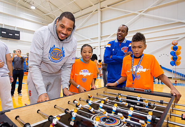 New York Knicks basketball star Carmelo Anthony plays foosball with kids at a Garden of Dreams Foundation event.