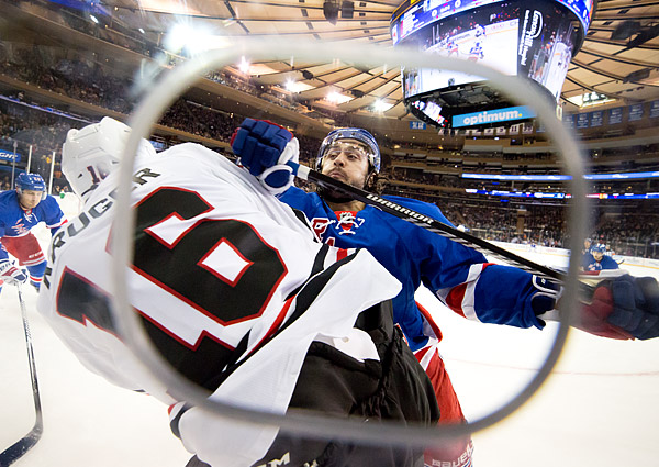 New York Ranger Mats Zuccarello checks Chicago Blackhawk Marcus Krüger into the glass in the Rangers' 3-2 preseason win at Madison Square Garden